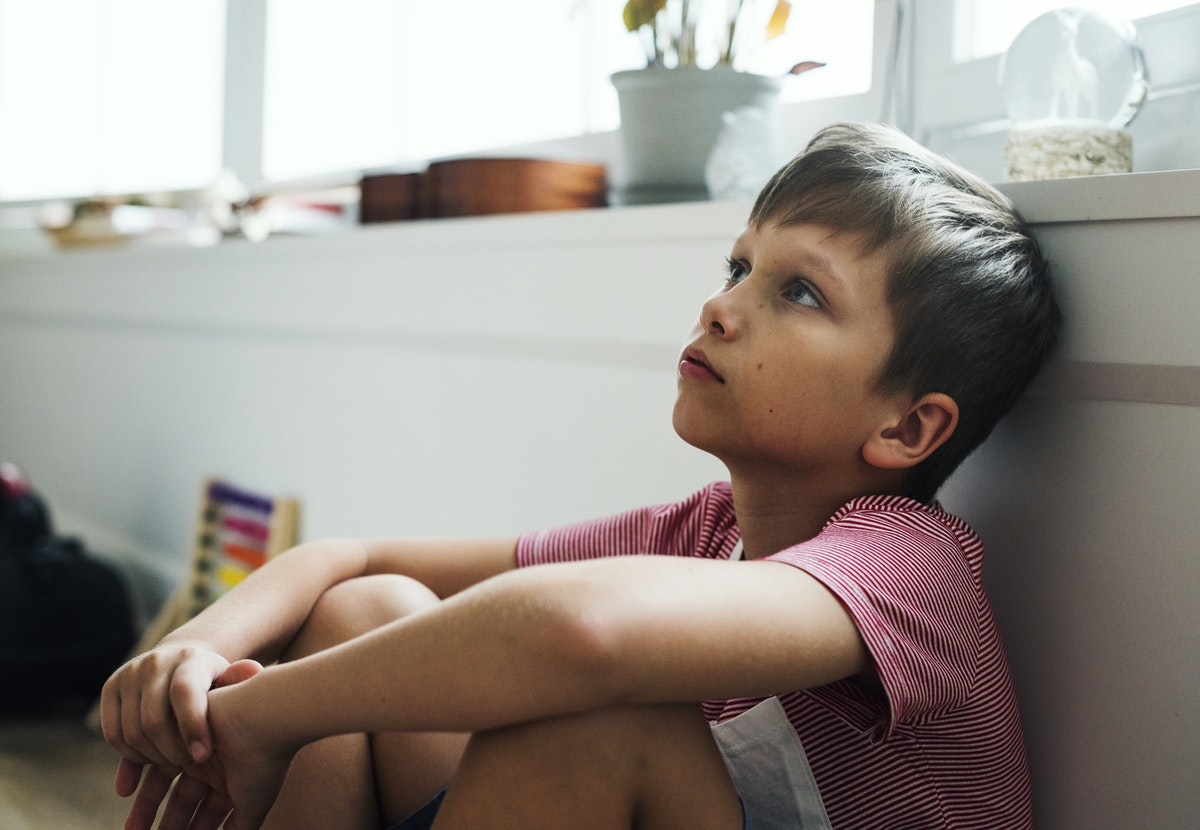 child sitting against a wall at a host home