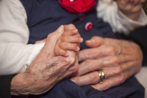 Baby and grandmother holding hands